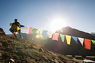 A Tibetan man hangs prayer flags near the Namgyal Tsemo Gompa in Leh, India.