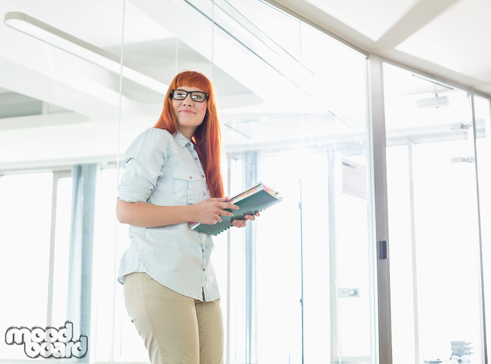 Creative businesswoman looking away while holding files in office