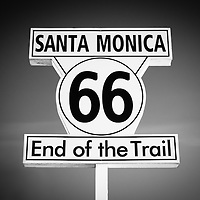 Route 66 sign in Santa Monica black and white picture. The sign says Santa Monica 66 End of the Trail and is located on Santa Monica Pier in Los Angeles County Southern California.
