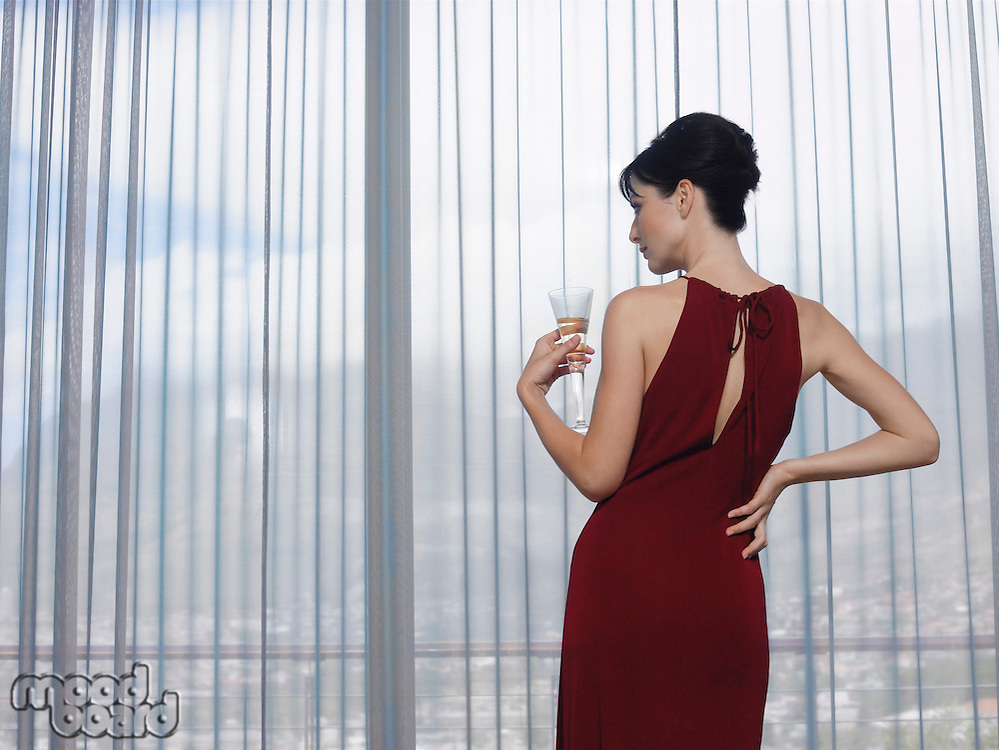 Woman wearing elegant dress looking out of window indoors