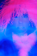 Portrait of a young woman wearing a glowing wig as she looks through a motion blur of light.Black light
