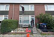 Nederland, Deest, 22-9-2018Een glazenwasser, glazenwassers, lapt de ramen van een woonhuis. Foto: Flip Franssen