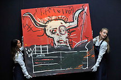 """© Licensed to London News Pictures. 06/10/2017. London, UK. Technicians present """"Cabra"""" by Jean-Michel Basquiat, from the collection of Yoko Ono, at a preview at Sotheby's in New Bond Street of contemporary, impressionist and modern art works to be auctioned in New York in November 2017 Photo credit : Stephen Chung/LNP"""