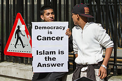 "© Licensed to London News Pictures . 20/06/2010 . London , UK . A boy holding a "" Democracy is cancer Islam is the answer "" placard . A Muslims Against Crusades demonstraion calling for Sharia Law for All , on Richmond Terrace , Whitehall , opposite Downing Street . Photo credit: Joel Goodman/LNP"