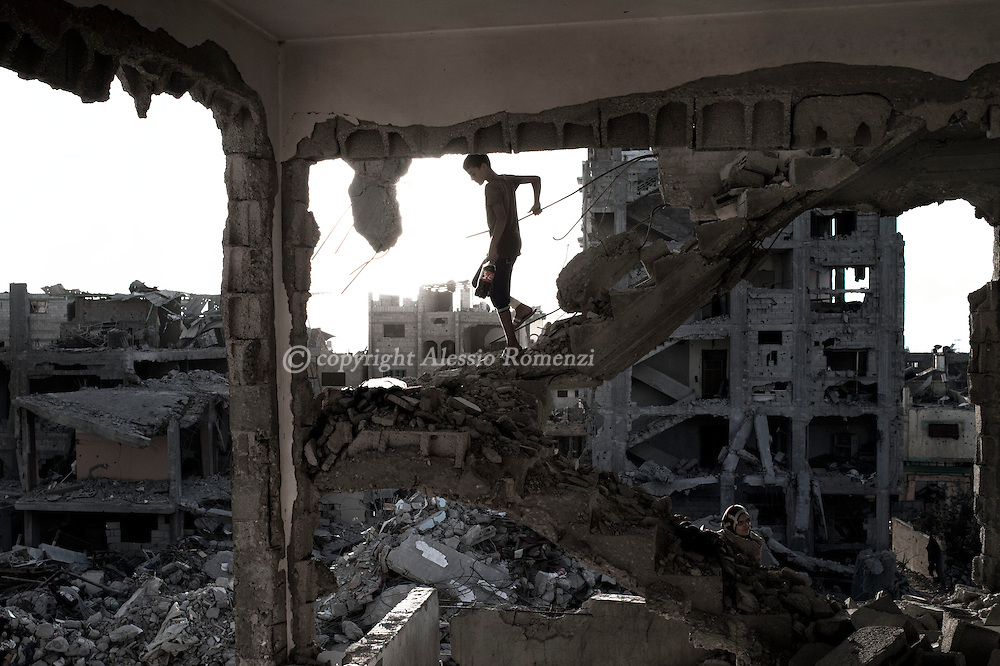 Gaza Strip, Gaza City: Palestinians are seen inside their destroyed by strikes house in Al Shaaf neighbourhood during a 72 hours ceasefire on August 11, 2012. ALESSIO ROMENZI