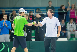 Blaz Kavcic of Slovenia (green) and captain Blaz Trupej during 2nd match of Davis cup Slovenia vs. Portugal on January 31, 2014 in Kranj, Slovenia. Photo by Vid Ponikvar / Sportida