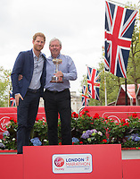 HRH Prince Henry of Wales (Prince Harry) stands with CBE Brendan Foster on the podium as Foster wins the Lifetime Achievement Award. The Virgin Money London Marathon, 23rd April 2017.<br /> <br /> Photo: Ben Queenborough for Virgin Money London Marathon<br /> <br /> For further information: media@londonmarathonevents.co.uk