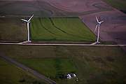 Two wind generators stand adjacent to a small farmhouse amid agricultural fields.  U.S. farmers often lease land to wind developers and collect funds for each turbine built on their land or receive a small percentage of annual revenue from power generation.
