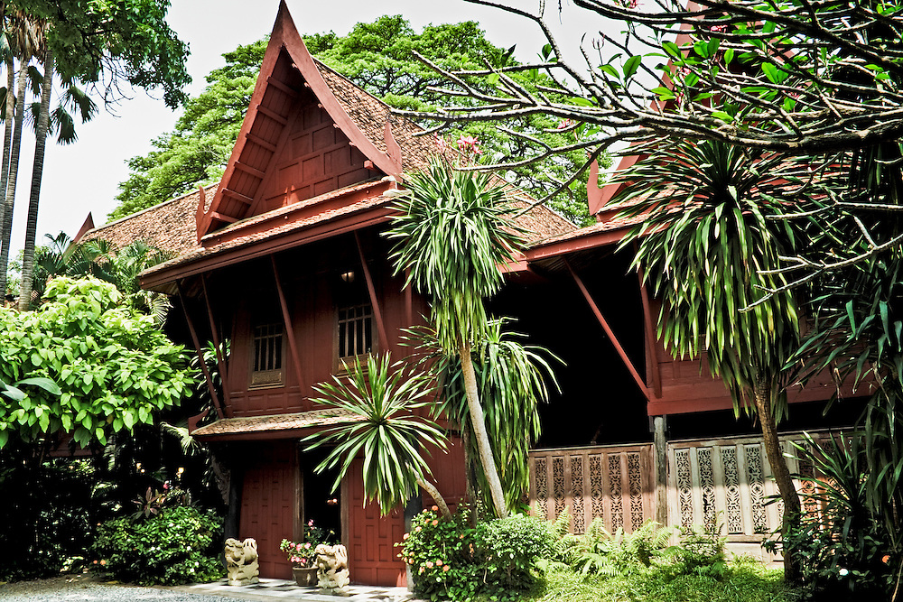 Three quarter view of the house built by Jim Thompson where he lived in Bangkok until his mysterious death in Malaysia.  Peaked roof, wooden panel walls in traditional Thai style.  It is a peaceful oasis within the crowded noise of the city.