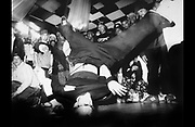 Breakdancer in club, with young men and women, London, UK, 1995.
