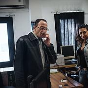 Mohamed en train de parler au téléphone avec sa mère à Damas, pour lui raconter; à droite Marina Mina Rabab, l'interprète. Les officiers du G.I.C.I.C. lui ont permis de faire cet appel depuis leur bureau