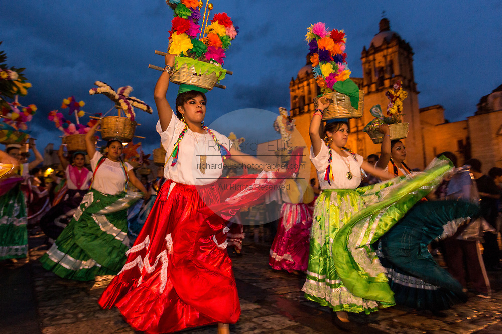Young women dressed in traditional costumes perform the Flor de Pina dance in a comparsas past the Santo Domingo de Guzmán Church during the Day of the Dead Festival known in Spanish as Día de Muertos on November 2, 2013 in Oaxaca, Mexico.