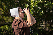 An Amish woman looks though binoculars Sarasota, Florida