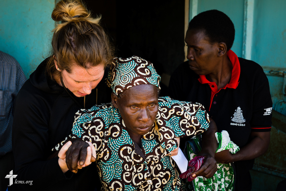 Nurse Casey Peters of Dover, N.H, and a community health worker from Kenya helps an elderly patient to the pharmacy during the Mercy Medical Team clinic Wednesday, June 11, 2014, at the Luanda Doho Primary School in Kakmega County, Kenya. LCMS Communications/Erik M. Lunsford