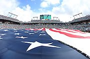 A giant American flag covers the field during the playing of the National Anthem in this general view photograph of Sun Life Stadium taken from field level before the Miami Dolphins 2015 week 13 regular season NFL football game against the Baltimore Ravens on Sunday, Dec. 6, 2015 in Miami Gardens, Fla. The Dolphins won the game 15-13. (©Paul Anthony Spinelli)
