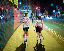 "© Licensed to London News Pictures . 27/10/2018. Manchester, UK. A man and a woman walk along Princess Street with "" Satan's bitches "" painted in mock blood on the backs of their t-shirts . Revellers on a night out , many in fancy dress , on the weekend before Halloween . Photo credit: Joel Goodman/LNP"