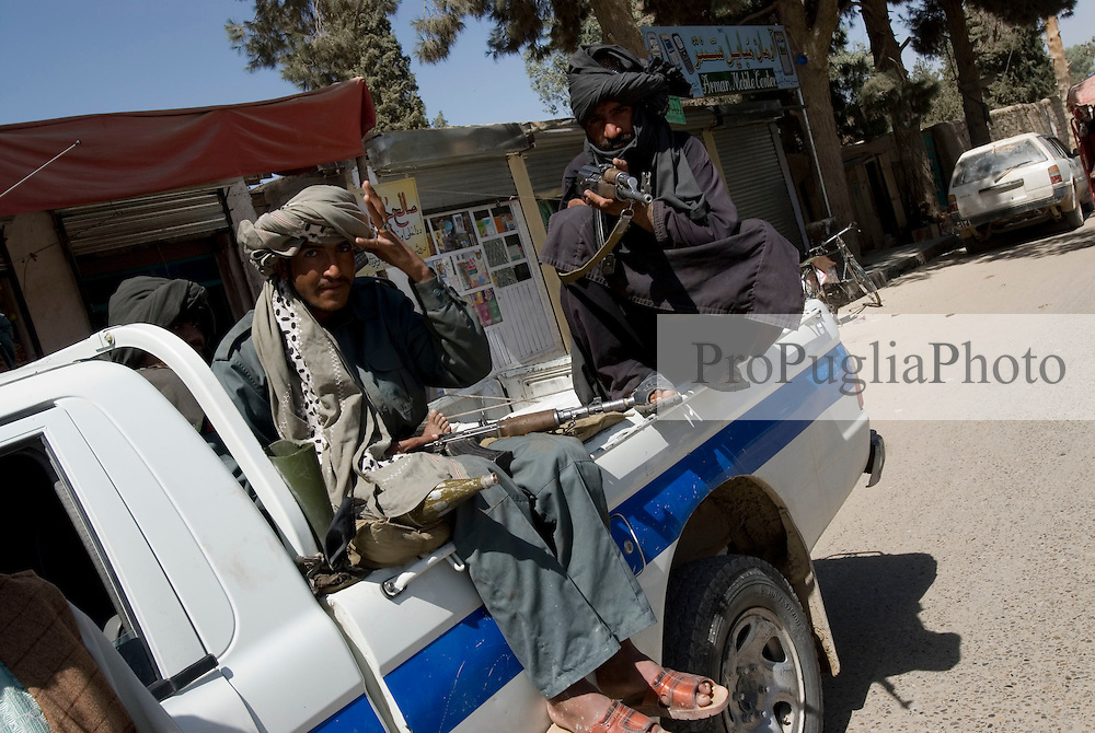 Helmand Province, Lashkargah City..Local policemen, armed with AK-47 and RPG,  patrolling the street on board of their truck.