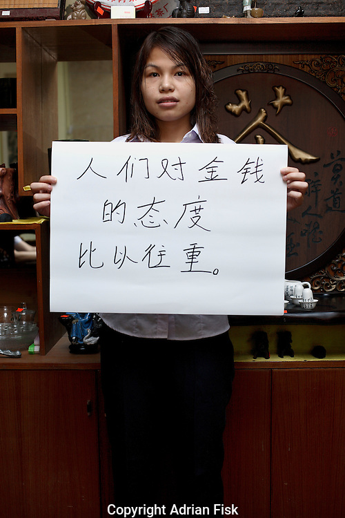Su Dong Ping - 22 Yrs. <br /> Works in a tea merchants shop.<br /> Guangdong Province.<br /> <br /> 'Peoples attitude towards money is increasing'..