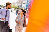 Businessman and businesswoman walking while discussing plans before meeting