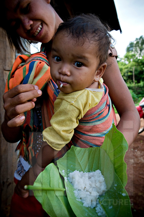 A mother tries to feed her kid with her hand. She carries rice in a leave. Jarai ethnic tribe, Pleiku area, Vietnam, Asia