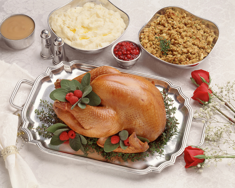 Fancy dinner table red roses linen napkin celebrate celebration party elegant fancy presentation Thanksgiving Christmas style holiday Sunday dinner roast turkey stuffing mashed potato gravy cranberry salt pepper pweter platter