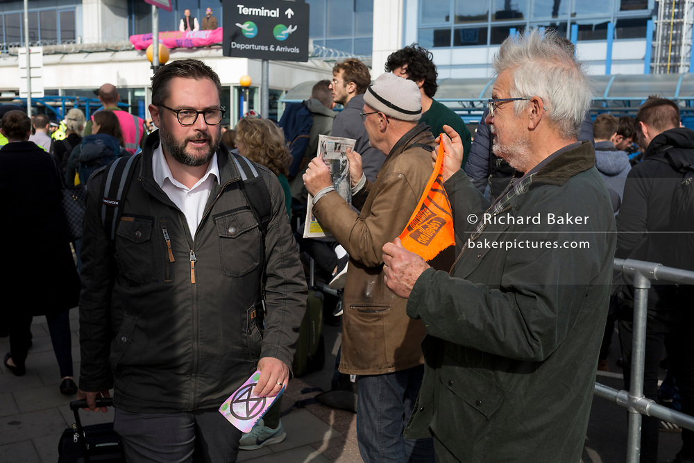 Environmental activists hand out leaflets to air passengers while protesting about Climate Change during the occupation of City Airport (London's Business Travel hub) in east London, the fourth day of a two-week prolonged worldwide protest by members of Extinction Rebellion, on 10th October 2019, in London, England.
