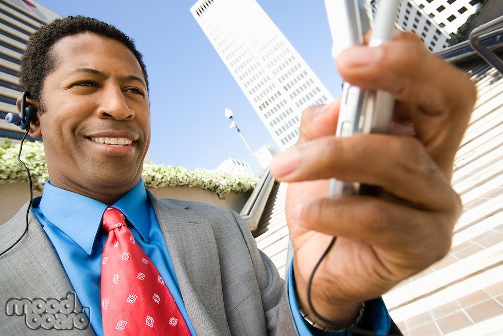 Businessman using mobile, outdoors, smiling