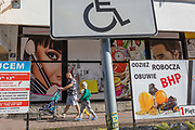 A  Polish father and his children walk past advertising signs, on 21st September 2019, in Szczawnica, Malopolska, Poland.