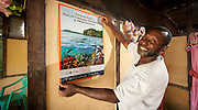 "Lobo Village community member Bram Wariensi shows off a conservation poster distributed by RARE Conservation and Conservation International, which he proudly displays in his home. The poster celebrates a locally designated ""Fish Savings Area"" as the first no take zone in the Kaimana Marine Consersation Area."