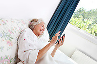 Happy senior woman using cell phone in bed at home