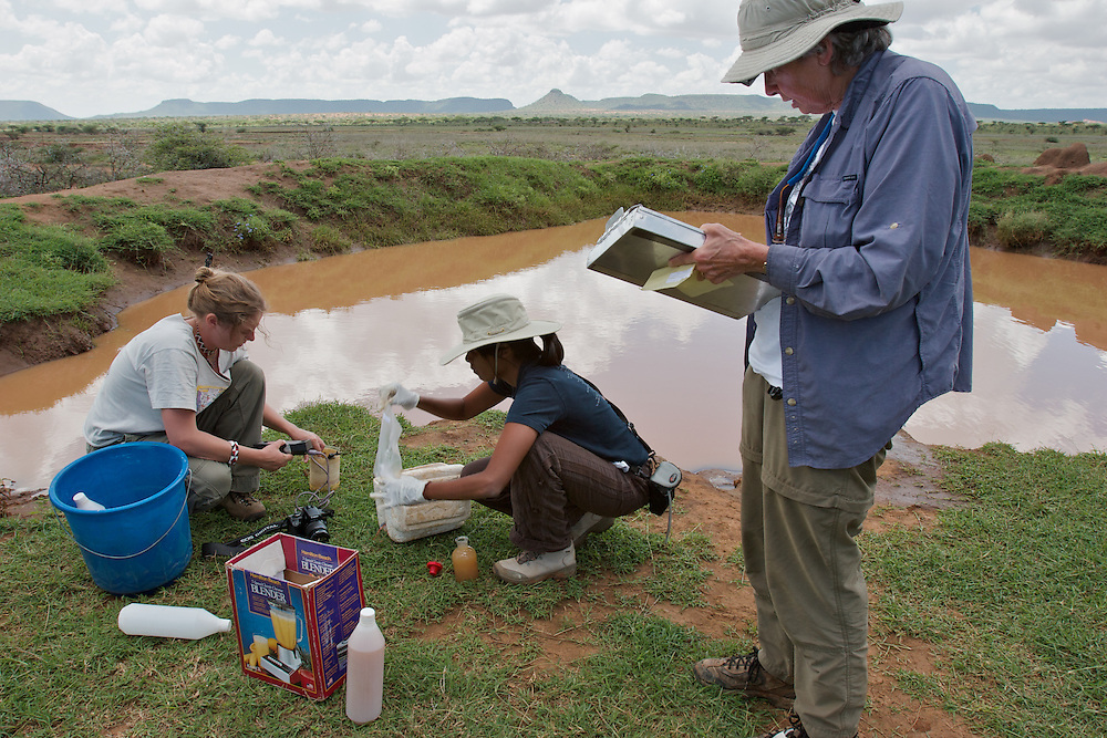 Earthwatch volunteers collect water sample data at a small dam in Samburu district, Kenya.