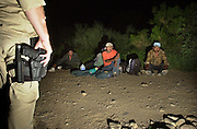 U. S. Border Patrol agents wait for transportation for deportation for illegal immigrants who crossed illegally from Mexico on to the Tohono O'odham Nation near Sells in the Sonoran Desert in Arizona, USA.  The area has the highest death rate for undocumented migrants along the U. S. - Mexico border.