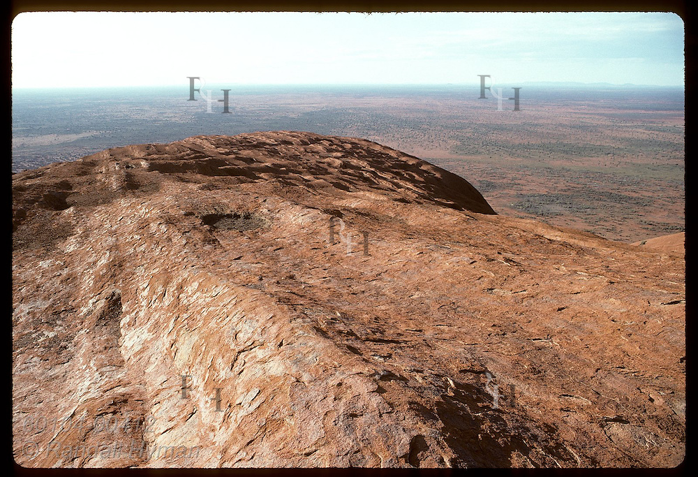 Seen from atop Ayers Rock on a summer morn, sandstone leads to precipice overlooking desert. Australia