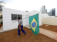 Jul 30, 2016; Rio de Janeiro, Brasil; Marcelo De Silva carries the Brazilian flag to the new houses built by the city of Rio de Janeiro at Vila Autodromo near Olympic Park and the Main Press Center. Mandatory Credit: Peter Casey-USA TODAY Sports