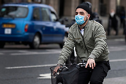 © Licensed to London News Pictures. 10/03/2020. London, UK. A man wearing a medical face mask while cycling over Westminster Bridge in London . New cases of the COVID-19 strain of Coronavirus are being reported daily as the government outlines it's plans for controlling the outbreak. Photo credit: Ben Cawthra/LNP