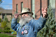 "Merrick, New York, USA. October 23, 2016. FRED S. CHANDLER, 66, of North Bellmore, wearing several political campaign buttons supporting Democratic presidential candidate Hillary Clinton, gestures with hand while talking during rally to demand public water and stop New York American Water (NYAW) rate hike. On denim jacket included buttons for Hofstra University DEBATE 2016 - and ""So My Daughter Knows She Can Be President. Hillary 16"" - ""TRUMPBUSTERS"" - ""CLINTON KAINE 16"" - and Monopoly Man character with ""NEVER TRUMP"" text."