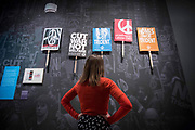 UNITED KINGDOM, London: 21 March 2017 A member of staff at The Imperial War Museum takes a close look at a collection of placards from the anti-Trident demonstration in London on 27th of February 2017. The placards form part of the 'People Power: Fighting for Peace' exhibition at the Imperial War Museum which explores the evolution of the anti-war movement from the First World War to the present day. Rick Findler / Story Picture Agency