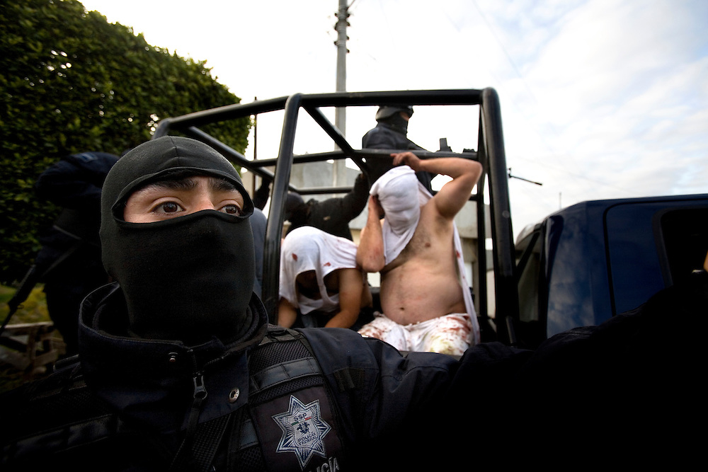 Federal police officers take a suspects into custody in connection with a shooting in Tijuana, Mexico, Monday, March 9, 2009. Mexico's cartels are losing their grip on the prized U.S. drug market, largely because of a cross-border crackdown and a regional shift in worldwide cocaine consumption.