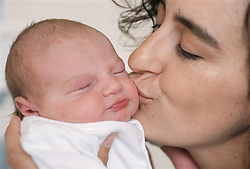 Mother holding and kissing new born baby on Maternity Unit in hospital,