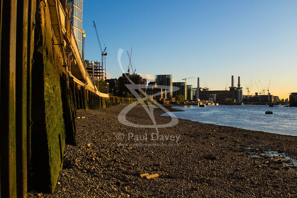 Battersea, London, April 29th 2015. After a day that started off with gloomy, damp weather, Londoners are rewarded with a beautiful spring sunset. PICTURED: The evening sun lights the algae covered walls of the Thames with Battersea Power Station silhouetted in the background.
