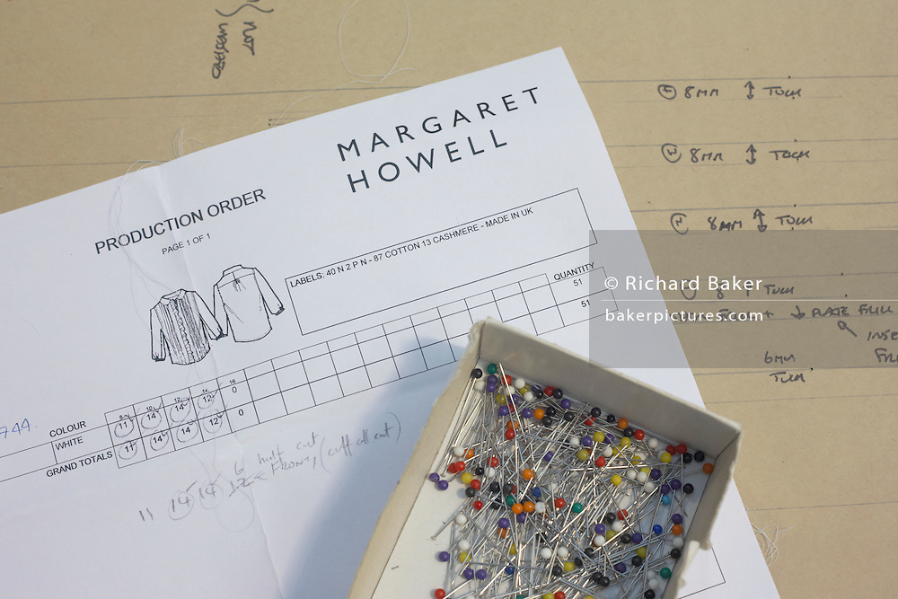 Garment production order form and pins in the design studio at couturier Margaret Howell's Edmonton workshop factory