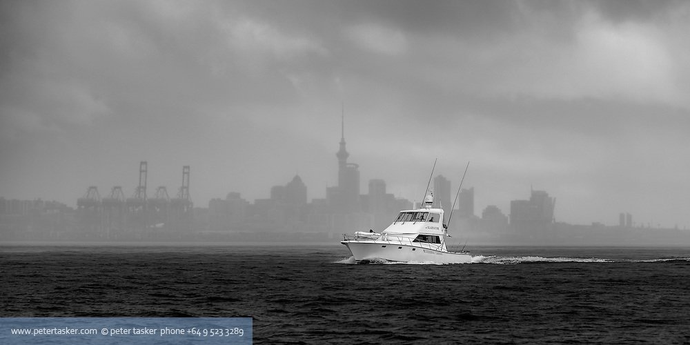The launch Gladiator, heading out of Auckland Harbour, on a stormy winters afternoon.  The background silouette of downtown Auckland, including the Skytower, is visible through the heavy rain
