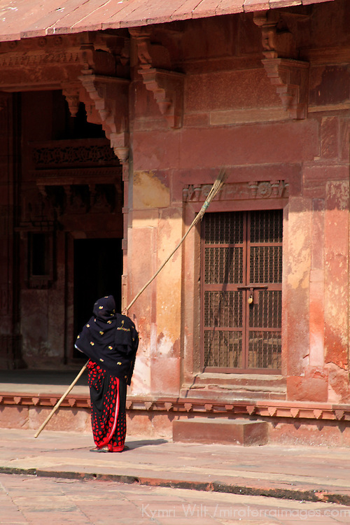 Asia, India, Fatehpur Sikri. woman sweeping facade at Fatehpur Sikri.
