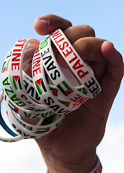 "London, August 23rd 2014. ""Save Palestine"" bracelets are offered for sale to raise funds as protesters outside Downing Street demand that Britain stops arming Israel."