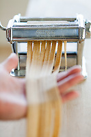 Fresh pasta being made with a hand cranked pasta machine.