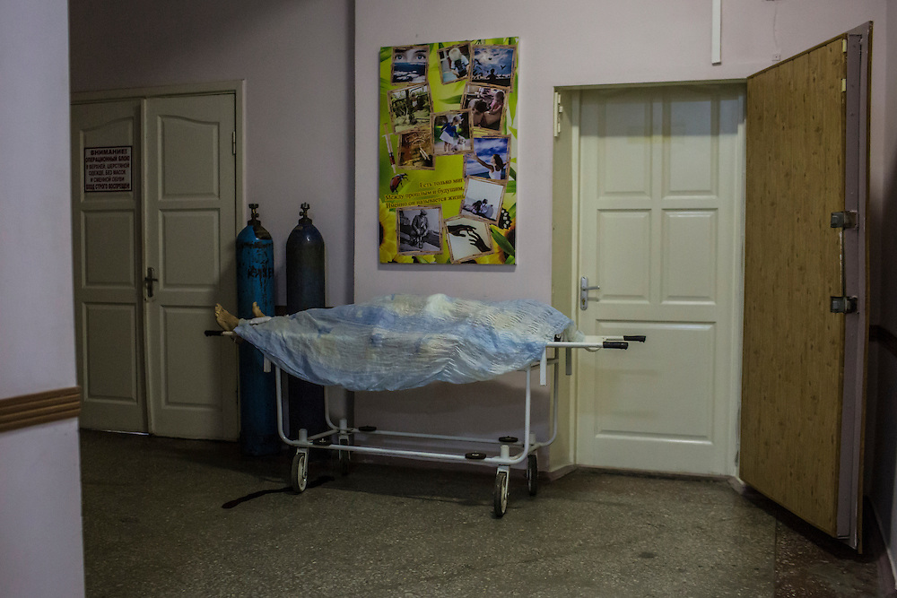 The body of a woman who was killed by a rocket attack lays on a gurney in a hallway in Vishnevskogo Hospital on January 26, 2015 in Donetsk, Ukraine. The rocket hit the home of her daughter, her home, wounding her nine-month-old daughter and killing her mother.
