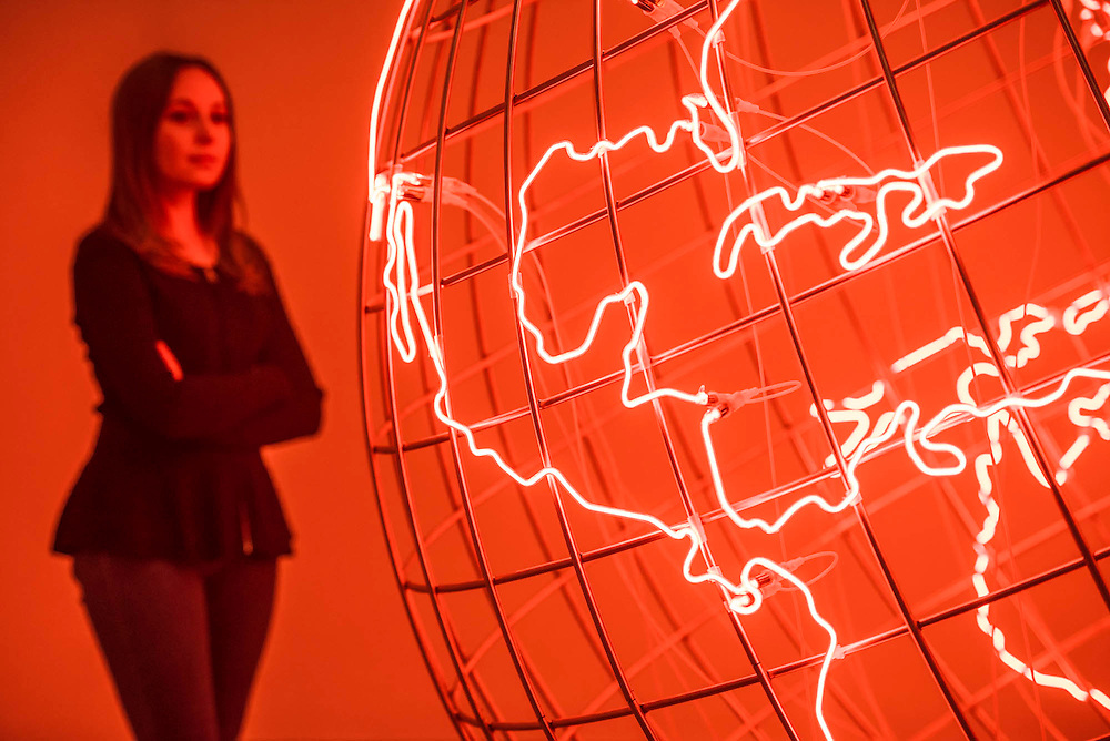 Hot Spot 2013 - Mona Hatoum a new Tate Modern exhibition. It presents around 100 works from the 1980s to the present day, including early performances and video, sculpture, installation, photography and works on paper. Mona Hatoum runs from 4 May to 21 August 2016.<br /> <br /> Highlights include:  Large-scale installations that fill entire rooms, including Impenetrable 2009, a suspended square formed of hundreds of delicate rods of barbed wire which hover above the floor, and Light Sentence 1992, in which walls of wire mesh lockers and a single lightbulb cast constantly moving shadows; Hot Spot 2013, a giant globe that uses red neon to outline the contours of the continents; a kinetic sculpture in which a rotating motor-driven arm draws circular lines across a large sandpit; and Homebound 2000, an installation of kitchen utensils and furniture which buzzes with electricity