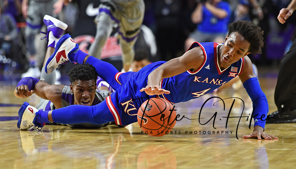 Guard Devonte Graham #4 of the Kansas Jayhawks reaches for a loose ball on the floor  with guard Wesley Iwundu #25 of the Kansas State Wildcats during the second half at Bramlage Coliseum in Manhattan, Kansas.