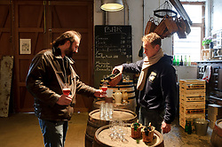 BRUSSELS, BELGIUM - DEC-30-2010 -  Jean Van Roy, the fourth generation owner of the Brasserie Cantillon, right, offers a sample of Kriek beer to Stephane Chabert, of Savoie, France, a visitor to the working brewery and museum of Belgian beer history. Cantillon specialises in a unique, wine-like style of beer called Lambic in its most elemental form, and Gueze when it's blended. The sour beer gets its funky, acidic bite from a spontaneous fermentation process and long aging that inoculates the wort, or pre-beer, with bacteria and yeast naturally available in the air. Variations include batches aged with cherries (Kriek), raspberries (Rose de Gambrinus), and apricots (Fou'Foune), all produced organically and all 100 percent Lambic. (Photo © Jock Fistick)
