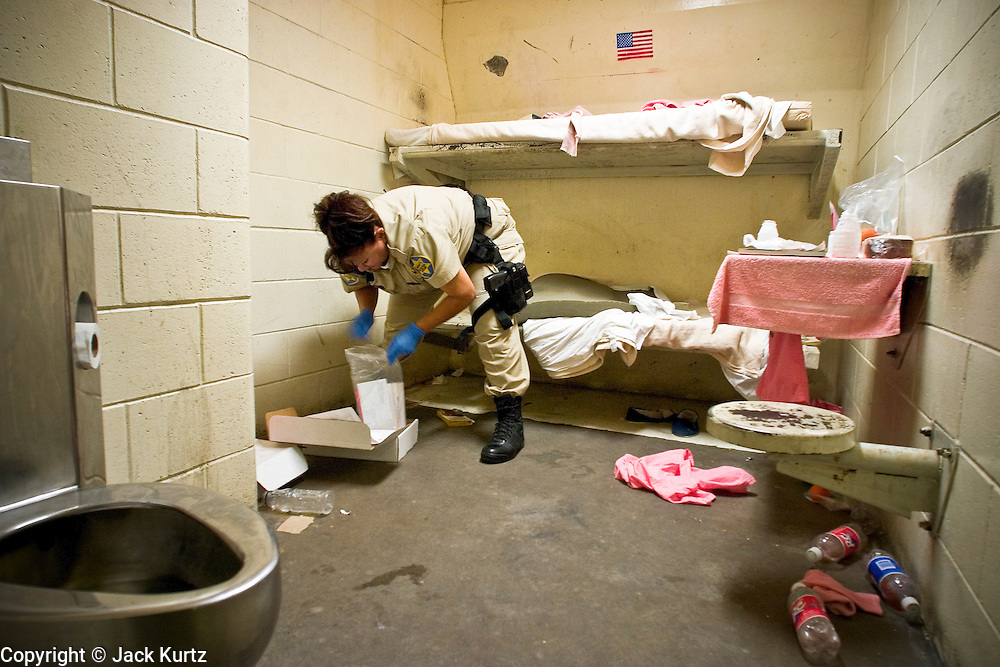 "24 MARCH 2004 - PHOENIX, AZ, USA: Maricopa County Sheriff's Dept Detention Officer C. Lopez inspect a juvenile prisoner's jail cell in the Maricopa County Jail in Phoenix, AZ, March 24, 2004. The juveniles volunteer to serve Maricpoa County Sheriff Joe Arpaio's chain gang. The sheriff, who claims to be ""the toughest sheriff in America,"" has chain gangs in both the men's and women's jails and now has a chain gang for juveniles sentenced and serving time as adults in the county jail system. The sheriff claims it is the only juvenile chain gang in the country.   PHOTO BY JACK KURTZ"